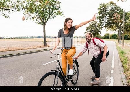Felice coppia giovane con noleggio biciclette e skateboard sulla strada di campagna Foto Stock