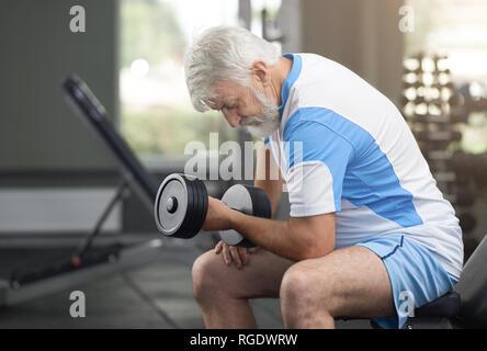 Un sano uomo anziano facendo esercizi in palestra moderna, utilizzando attrezzature sportive. Montare e atletico uomo seduto sul banco speciale, appoggiata sul ginocchio. Titolare di pensione o di rendita che lavora fuori si ostina a. Foto Stock