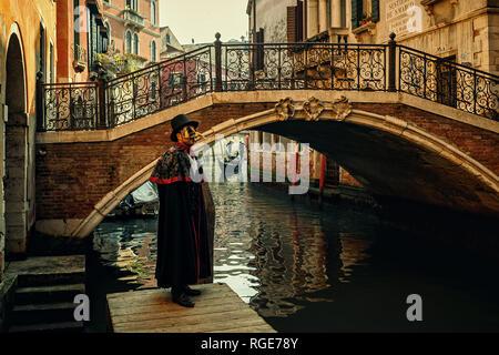 Unidentified uomo vestito in costume nero, cappello e maschera in posa di fronte del piccolo ponte veneziano sul stretto canale a Venezia, Italia. Foto Stock
