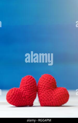 Il giorno di San Valentino concetto. mano fare due filati cuore rosso sul tavolo di legno e sfondo blu Foto Stock