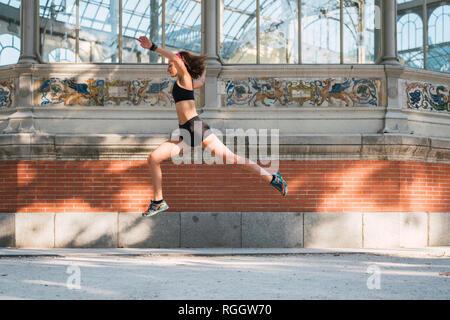 Montare la giovane donna che esegue un salto nel parco