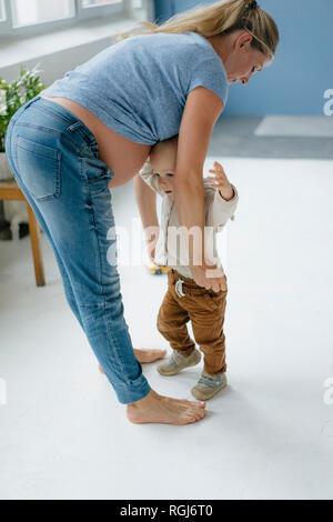 Gravidanza madre con bambino figlio in piedi sul pavimento