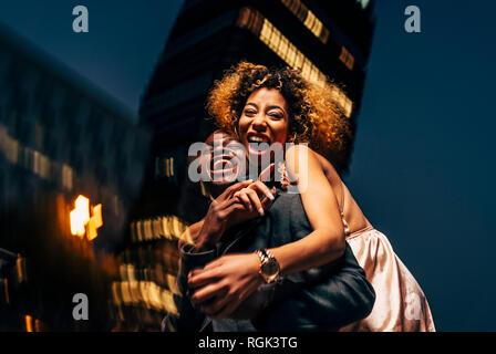 Ridendo coppia giovane avendo divertimento notturno in città