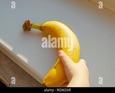 Baby mano azienda banana, close-up la luce del sole. Foto Stock