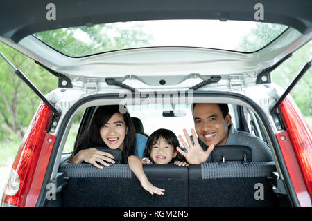Madre, padre e sua figlia all'interno di una macchina guardare fuori dal retro windows