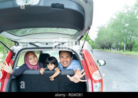 Madre, padre e sua figlia all'interno di una macchina guardare fuori dal retro windows Foto Stock