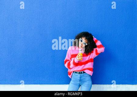 Ritratto di sorridente giovane donna con bottiglia di succo di arancia in piedi nella parte anteriore della parete di blu Foto Stock
