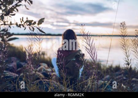 Giovane donna seduta al lago Inari, guardando a vista, Finlandia Foto Stock