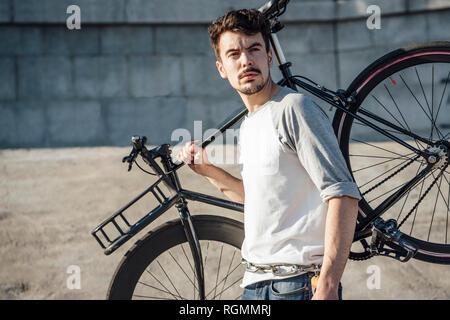 0893a016f85425 Nuvole cambiamenti di luce · Giovane uomo che porta commuter fixie bike a  parete in calcestruzzo Foto Stock