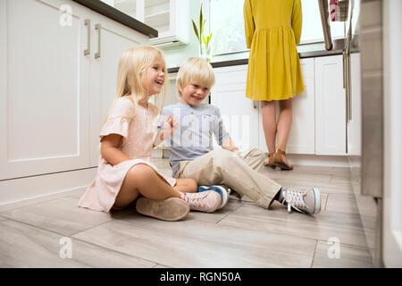 Fratello e Sorella seduta sul pavimento in cucina guardando al forno Foto Stock
