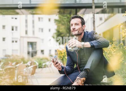 Imprenditore seduto fuori, prendendo una pausa, ascoltando la musica dal suo smartphone, bere caffè Foto Stock