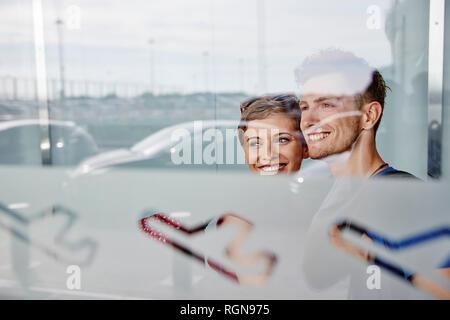 Ritratto di Coppia sorridente in aeroporto guardando fuori della finestra Foto Stock