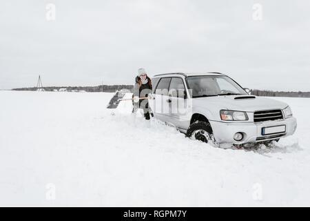 Donna con la pala vicino auto sul campo di neve Foto Stock