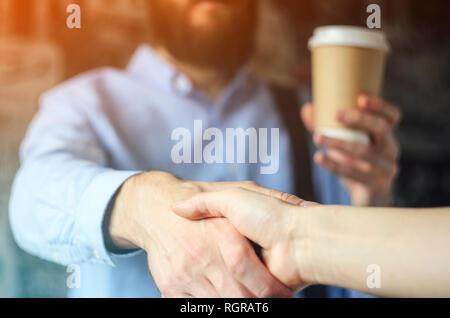 Imprenditore beve caffè e saluta la mano con un partner. Un incontro barba maglietta blu bicchiere di carta stretta di mano incontro di saluto. Pausa caffè Concept Foto Stock