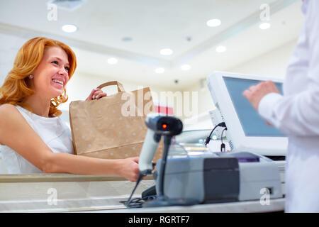 Accesso wireless a pagamento utilizzando lo smartphone e la tecnologia NFC. Close up. Cliente femmina pagando con smart phone nel negozio. Close up shopping Foto Stock