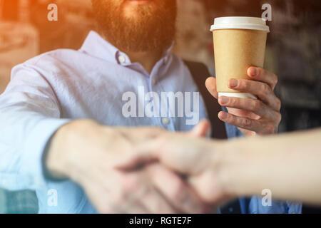 Imprenditore beve caffè e saluta la mano con un partner. Un incontro barba maglietta blu bicchiere di carta stretta di mano incontro di saluto. Caffè il concetto di Business Foto Stock