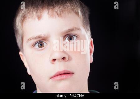 Studio dei colpi di giovane ragazzo con breve marrone capelli, indossando il ponticello verde Foto Stock