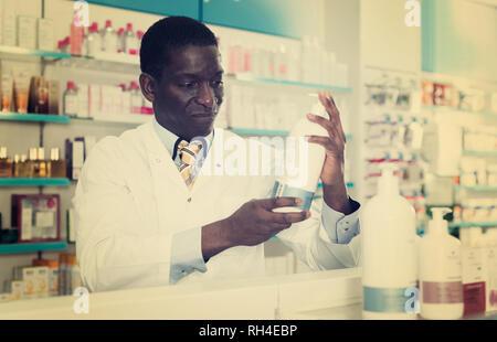 Esperto americano africano farmacista maschio lavora in farmacia moderna Foto Stock