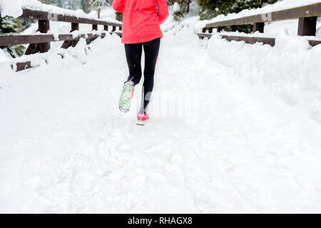 Giovane donna in esecuzione sulla neve in inverno le montagne di indossare abiti caldi guanti in snow meteo. Sport e fitness ispirazione e motivazione. Felice teen wo
