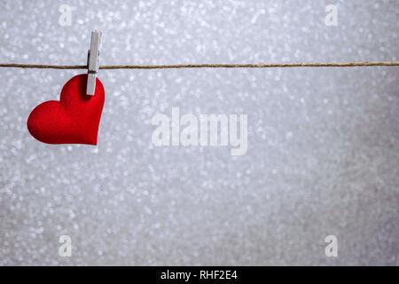 Unico cuore rosso appeso da stringa dalla molletta da bucato su sfondo argento. Romantico San Valentino in scena con spazio di copia Foto Stock