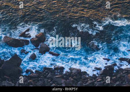Deep Blue onde dell oceano Atlantico colpendo il basalto scuro shore con luce solare d'oro riflettente onde off al tramonto. Capo Roca Foto Stock