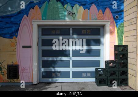 Questa casa vicino a Ocean Beach a San Francisco ha un murale colorato di tavole da surf intorno alla sua porta di garage. Foto Stock