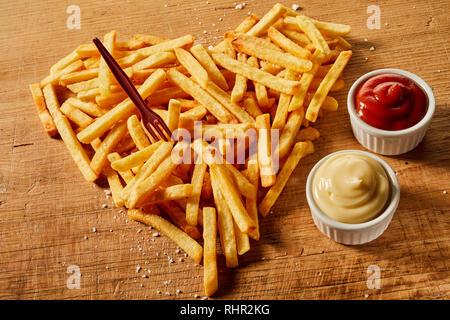Salato e stagionato a forma di cuore che serve di frittura di patatine con senape e ketchup sul legno con forcella di plastica Foto Stock