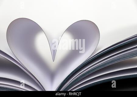 Forma di cuore dal libro di carta pagine isolati su sfondo bianco. Amore per la lettura, il concetto di scienza, di apprendimento, di romanticismo romanzo, il giorno di San Valentino Foto Stock