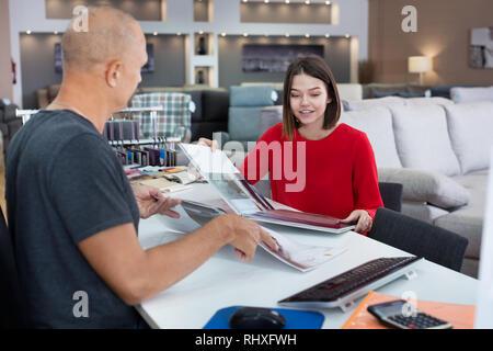 Consulente maschio aiutando giovane donna scegliendo la selleria in tessuto il negozio di arredamento. Focus sulla donna Foto Stock