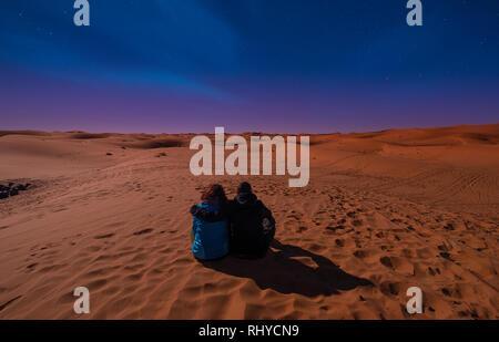 Paesaggio notturno con amorevole giovane, un ragazzo e una ragazza seduta sulle dune di sabbia guardando l'orizzonte . Cielo notturno con stelle nel deserto del Sahara in Marocco Foto Stock