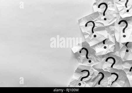Confine di accartocciata interrogativi sulle schede su uno sfondo bianco con copia spazio in una immagine concettuale Foto Stock
