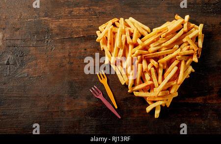 A forma di cuore la vita ancora di patatine fritte, pommes frites o patatine visto dal di sopra su vintage legno con copia spazio e forcelle in plastica Foto Stock
