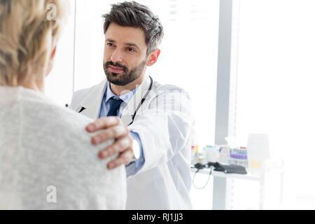 Metà adulto medico consolante coppia paziente in ospedale Foto Stock
