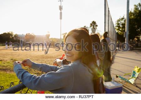 Ritratto sorridente, fiduciosi Latinx giovane donna guardando la partita di baseball Foto Stock