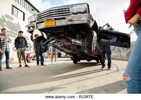 Latinx amici guardare bassa auto rider rimbalza nella soleggiata area di parcheggio Foto Stock