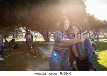 Latinx giovani volontari di sesso femminile prendendo selfie, parco di pulizia Foto Stock