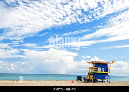 South Beach, Miami, Florida, bagnino casa in un colorato stile Art Deco su nuvoloso cielo blu e Oceano Atlantico in background, famosa in tutto il mondo percorso di viaggio
