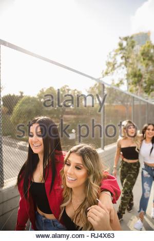 Felice Latinx donne giovani amici passeggiando lungo urbano recinzione cavalcavia Foto Stock