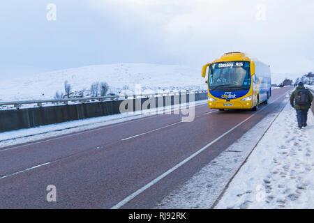 Scottish citylink irizar pullman 915 a Glasgow che viaggiano lungo una strada82 sul giorno di inverni con la neve intorno a Rannoch Moor, altopiani, Scozia in inverno Foto Stock