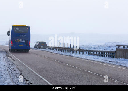 Scottish citylink pullman 915 veicolo che viaggia lungo un82 strada sulla giornata invernale e con neve intorno a Rannoch Moor, altopiani, Scozia in inverno Foto Stock