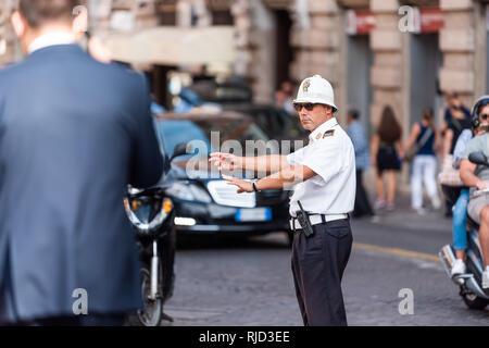 Roma, Italia - 4 Settembre 2018: Uno il traffico italiano uomo in una strada di città in piedi al di fuori dell'arma dei carabinieri funzionario di polizia dirigere le vetture su strada Foto Stock