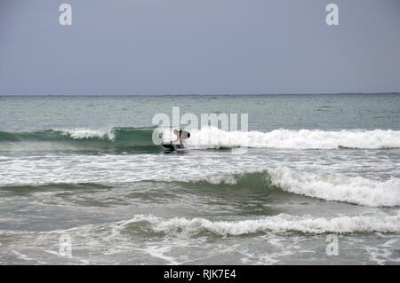 L'uomo surf su terreni accidentati e minaccioso dei mari Foto Stock