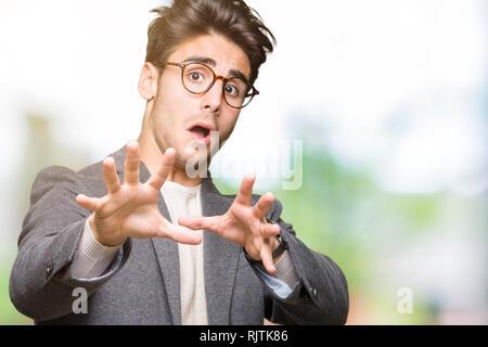 Giovane uomo d affari con gli occhiali su sfondo isolato paura e il terrore con la paura di espressione gesto di arresto con le mani, gridando in stato di shock. Pani Foto Stock