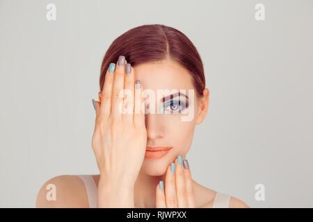 Bella donna di bellezza artistica con blue occhi verdi trucco tenendo le mani vicino, che ricopre la faccia che mostra manicure grigio blu smalto per unghie isolato su luce Foto Stock