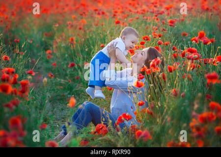 Ritratto all'aperto. Giovane madre e figlia godersi la vita del tempo insieme su un campo di papavero . Concetto di amore e di famiglia felice. Il papavero prato. Foto Stock