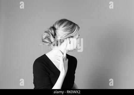 Ritratto di donna bella in un abito nero contro lo sfondo grigio Foto Stock