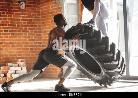 I giovani africani muscolare uomo capovolgimento di un pneumatico con una donna su di esso, lavorando fuori con pesatura