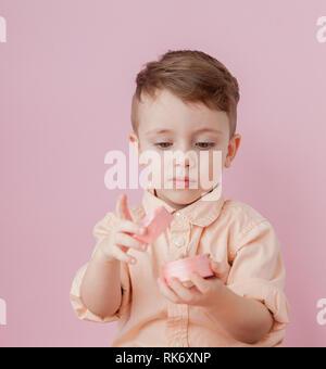 ... Felice ragazzino con un dono . Foto isolato su sfondo rosa. Ragazzo  sorridente tiene presente eb96c7adbf7