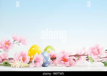 Uova di Pasqua e fiori di colore rosa decorazione su sfondo blu Foto Stock