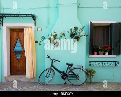 Bicicletta vicino casa turchese sull isola veneziana Burano, Italia. Foto Stock